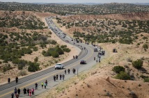 On Good Friday pilgrims travel the road from Nambé, New Mexico to El Santuario de Chimayo, Friday, April 18, 2014. As many as 40,000 pilgrims journey to El Santuario de Chimayo each year during the Easter weekend. (AP Photo/Jeremy Wade Shockley)